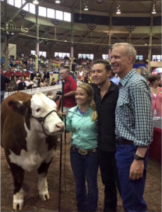 Posing for a picture with Scotty (the show steer), country music star Scotty McCreery, and Governor Bruce Rauner, 4-Her Taylor Donelson, of McClean County, was all smiles during the Illinois State Fair 'Sale of Champions.' Scotty was performing in the grandstands when he heard the grand champion steer was named after him and thought he'd come check it out. Such a cool moment for Illinois 4-H! Photo credit: Scotty McCreery Facebook